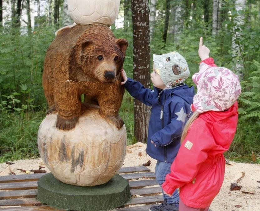 Kaksi lasta punaisessa ja sinisessä takissa ihmettelee veistettyä karhua