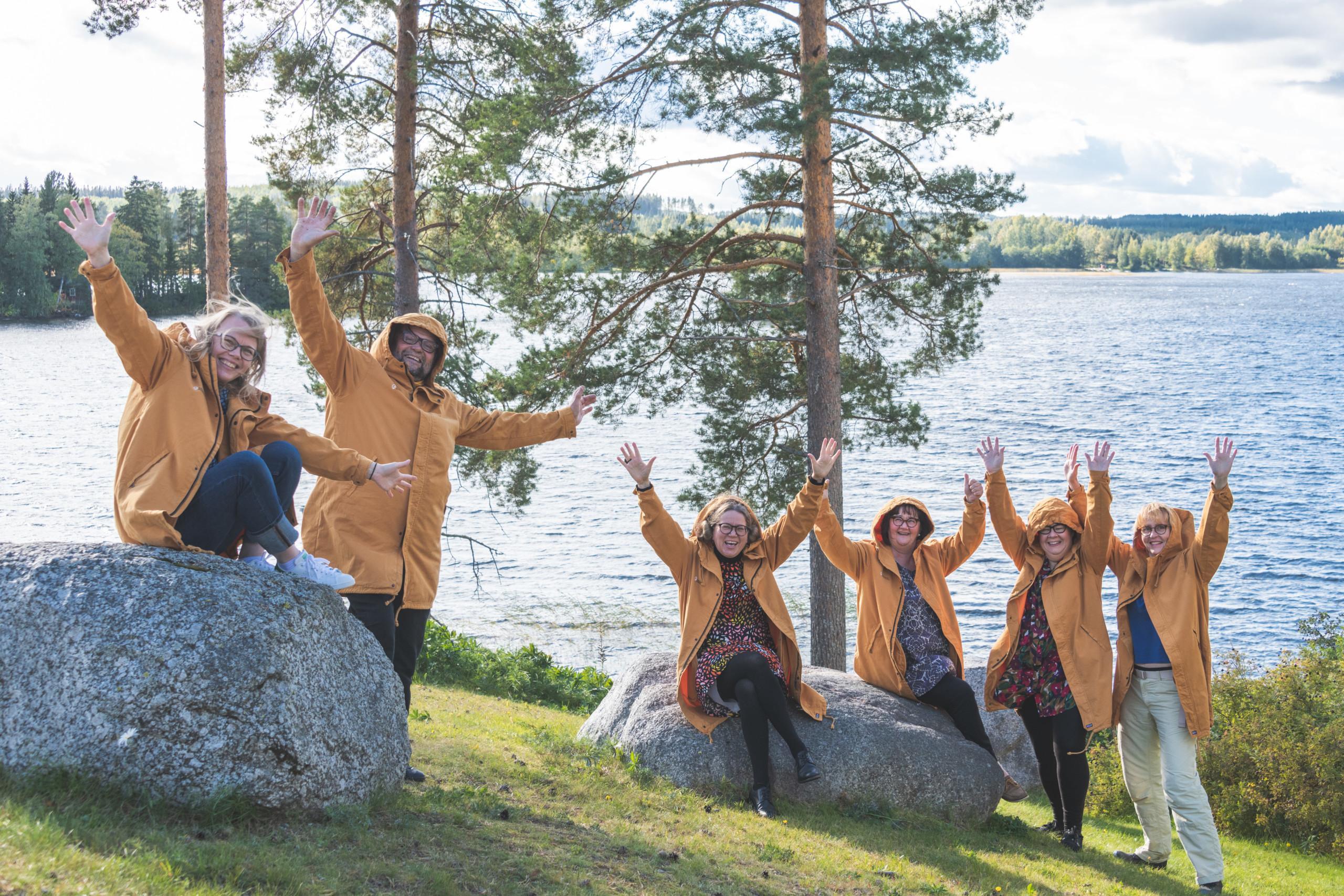 Ihmiset keltaisissa takeissaan kädet ylhäällä rantamaisemissa
