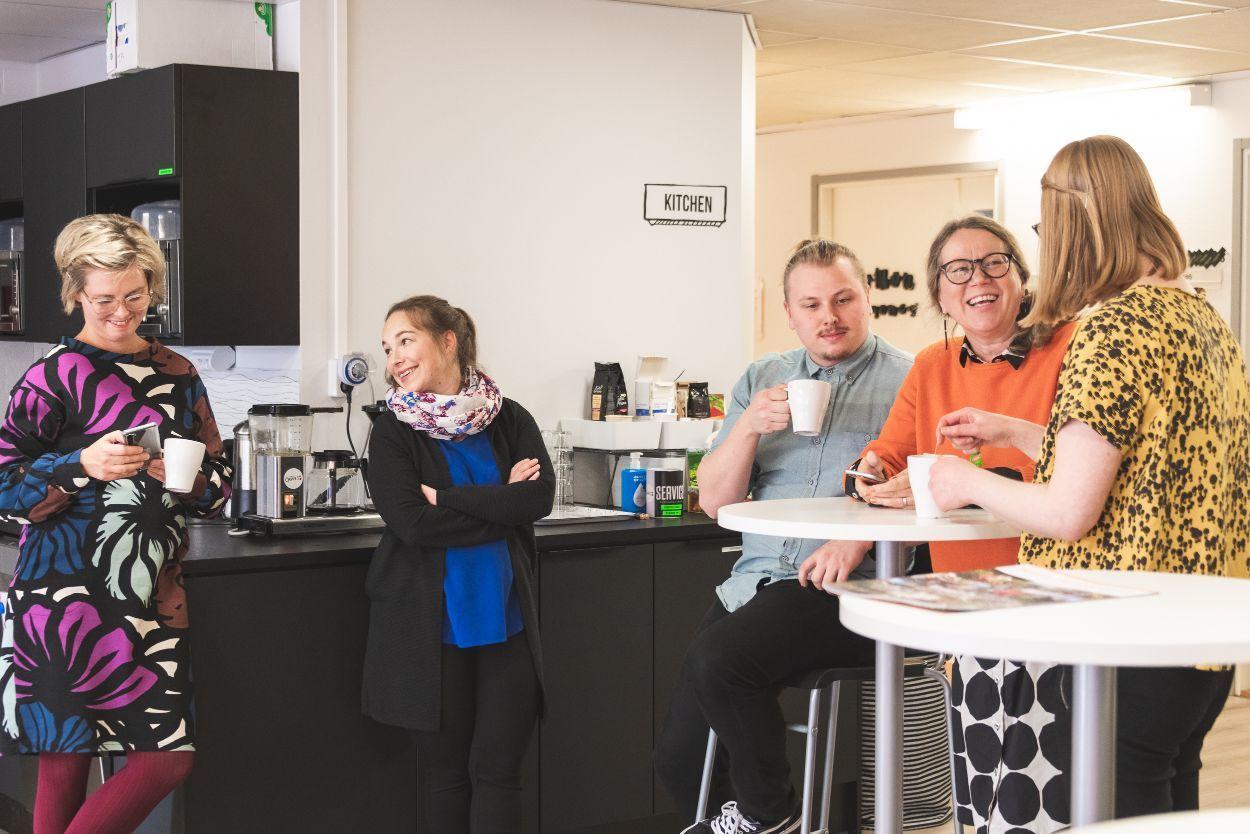 Viisi ihmistä keskustelee kahvihuoneessa.