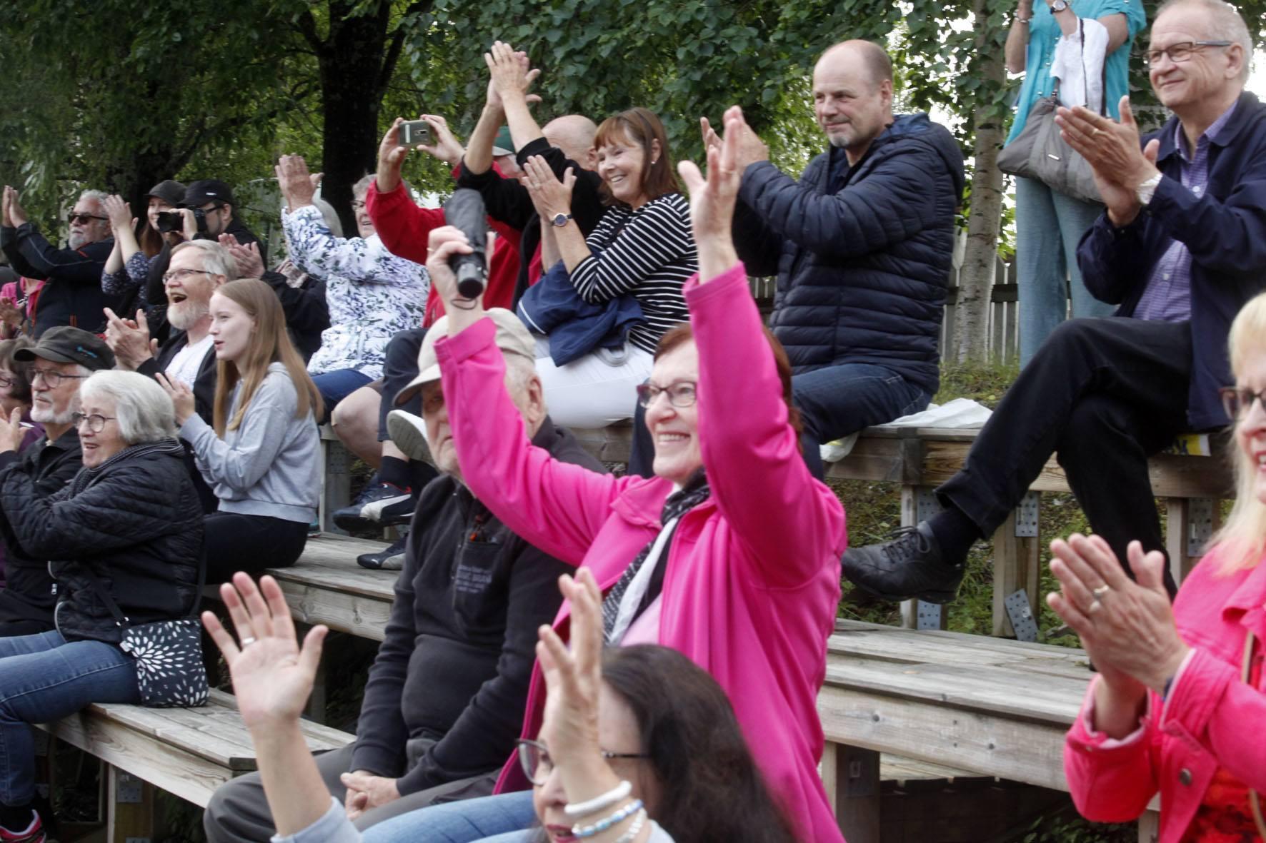 Katsomossa istuvat ihmiset hurraavat kädet ylhäällä. Keskellä nainen pinkissä takissa.