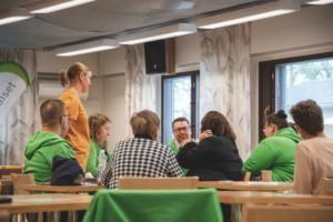 Ihmisiä luokkahuoneessa istumassa pöytien äärellä vihreissä huppareissa. Nainen seiso oranssissa paidassa keskellä.