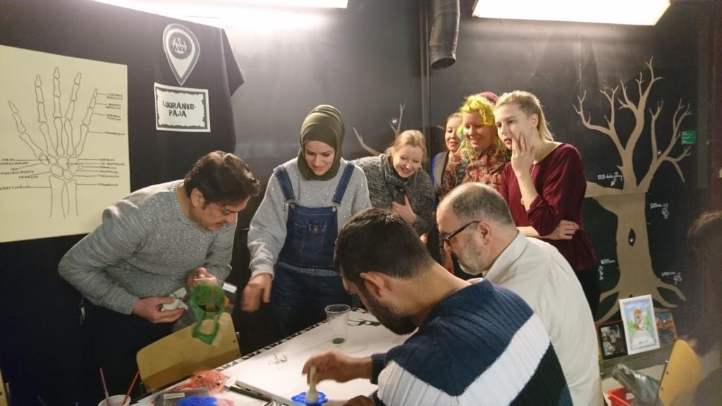 Ryhmä ihmisiä yhteisen taideteoksen ympärillä ja sitä tekemässä
