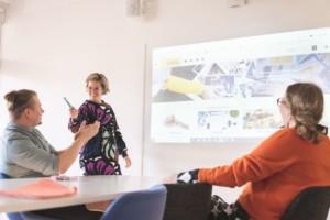 Kaksi ihmistä kuuntelee pöydän ääressä, kun kolmas esittelee MSL verkko-opistoa ja hymyilee.