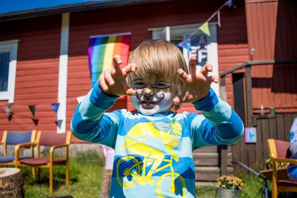Kirjavapaitainen lapsi, jolla eläimen kasvomaalaus näyttää kynsiä kameralle. Taustalla kesäpäivä, punainen lautaverhoiltu talo ja värikkäitä lippuja.