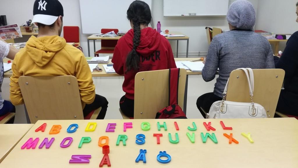 Lukutaito-oppilaat istuvat pöydän takana selkä kameraan päin. Etualalla pöydällä muovisia aakkosia.