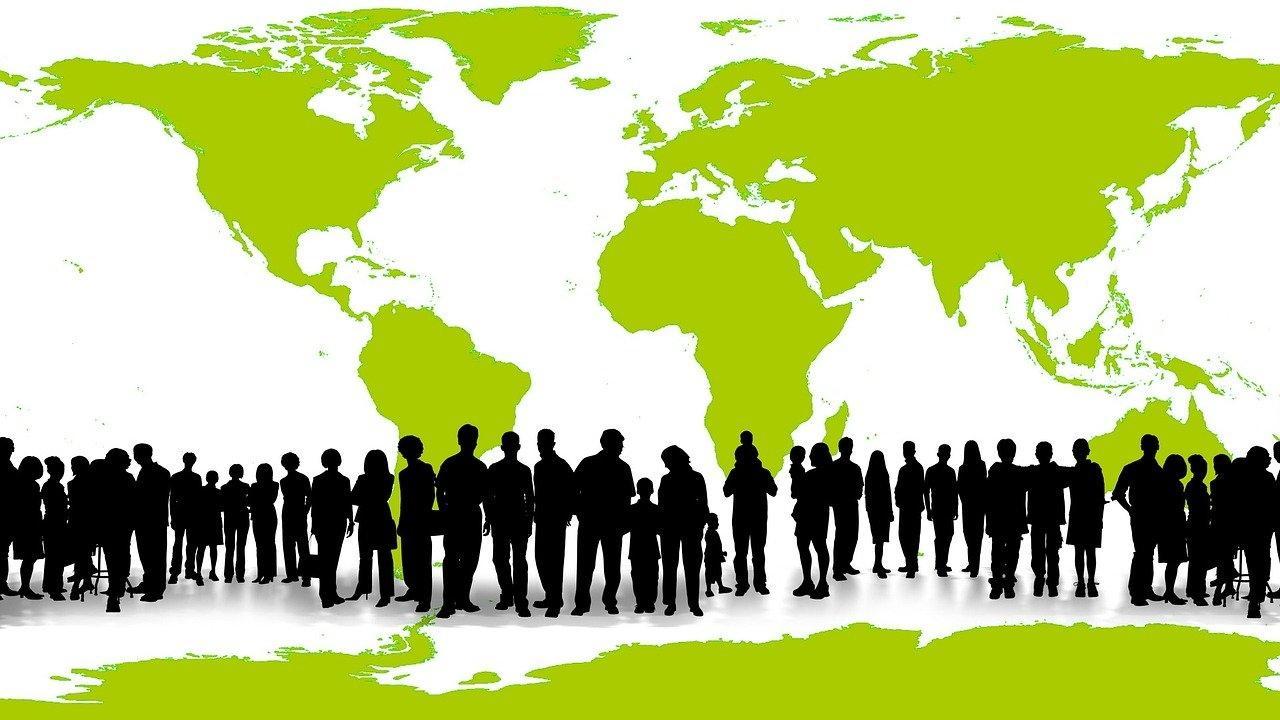 Rivistö ihmisten siluetteja vihreän maailmankartan edessä