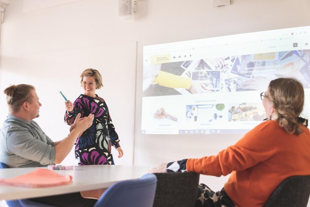 Yksi henkilö kouluttaa Moodlen käyttöä ja kaksi kuuntelee istuen pöydän ääressä.