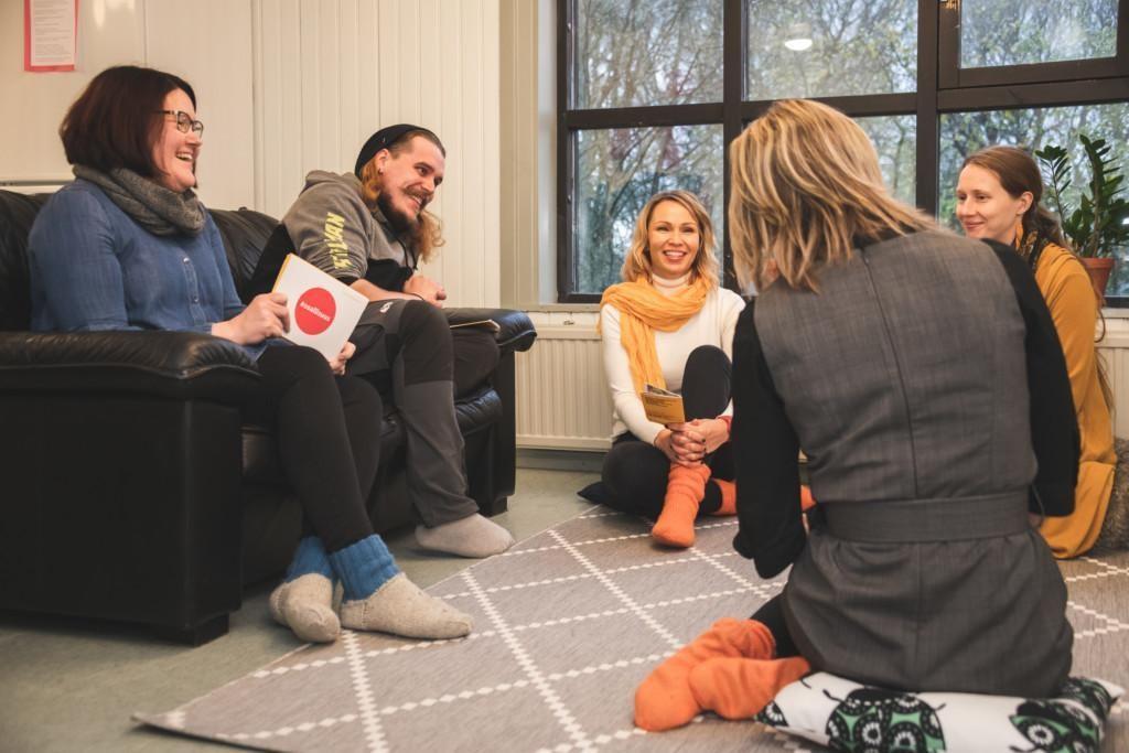 Ihmet juttelevat iloisina, nainen ja mies istuvat sohvalla, kolme naista lattialla.
