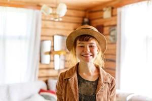 Nuori nainen olkihattu päässä hymyilee kameralle vanhassa hirsitalossa.