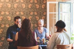 Neljä ihmistä istuu kahvipöydässä ja keskustelee iloisesti hmyillen.
